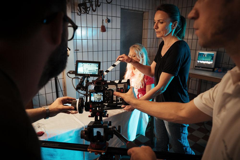 Hauptdarstellerung sitzt am Tisch - ein Ausschnitt aus Musikvideo